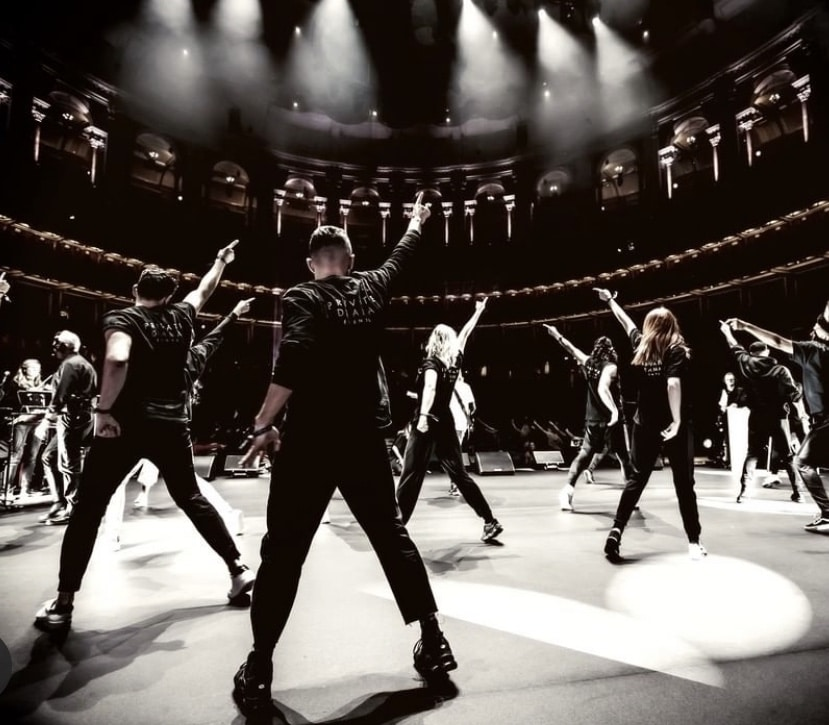 A black and white image of dancers standing on a stage with their hands in their air