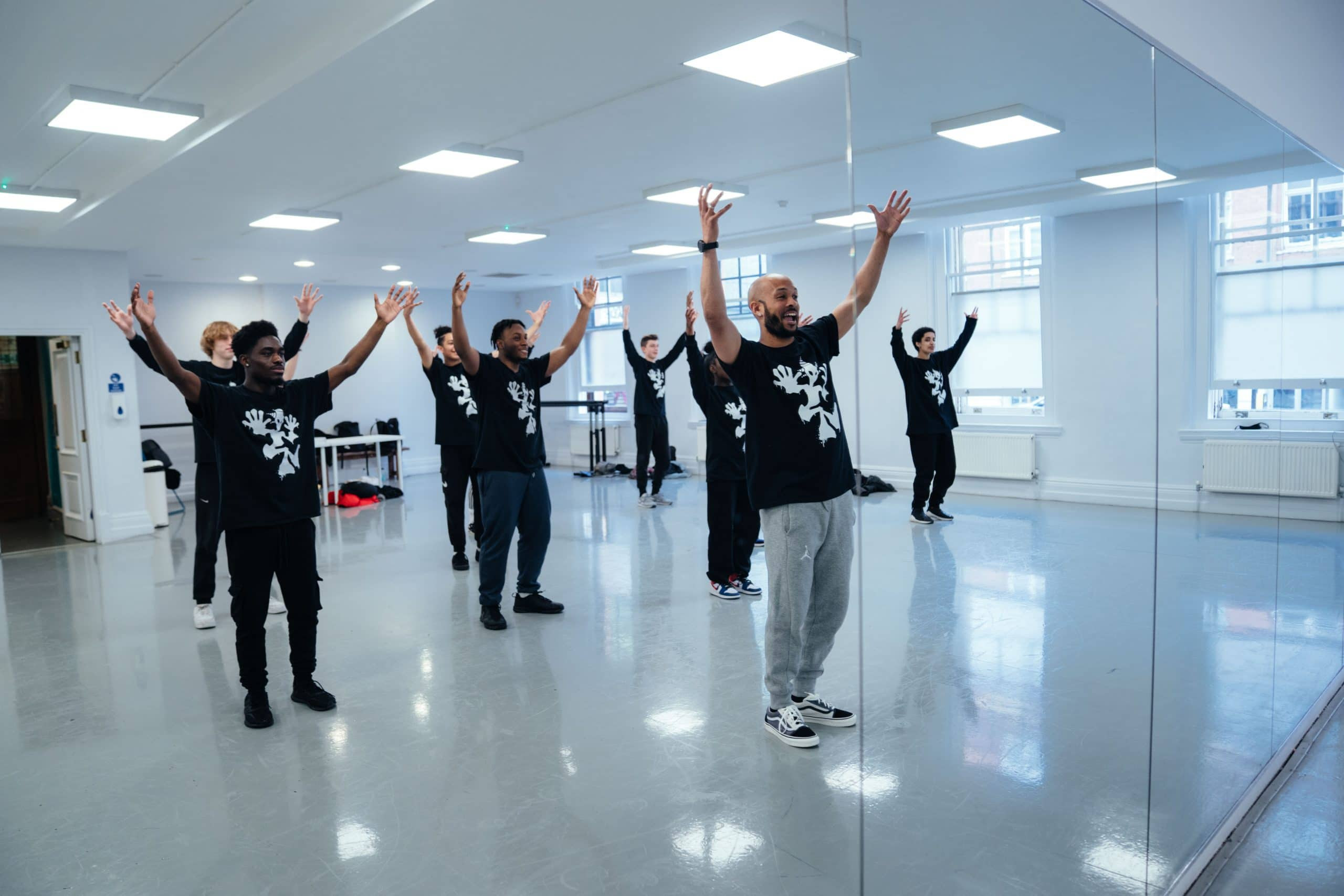 Bradley leads a group of young men in dnce in a studio. ZooNation Youth Company 2021 ; Rehearsals