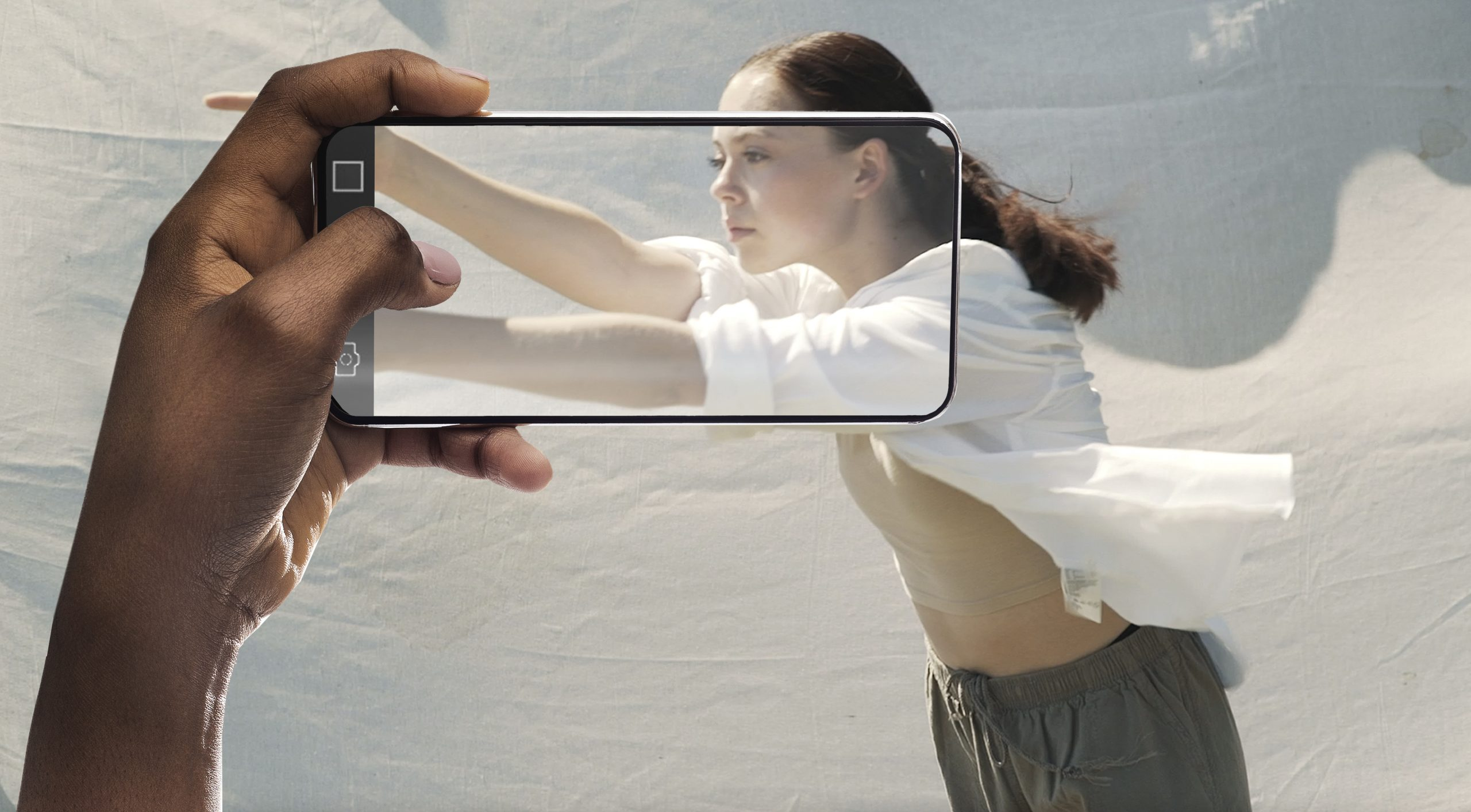 A girl in a white shirt reaches out against a pale background while a hand holds a mobile phone up to capture it
