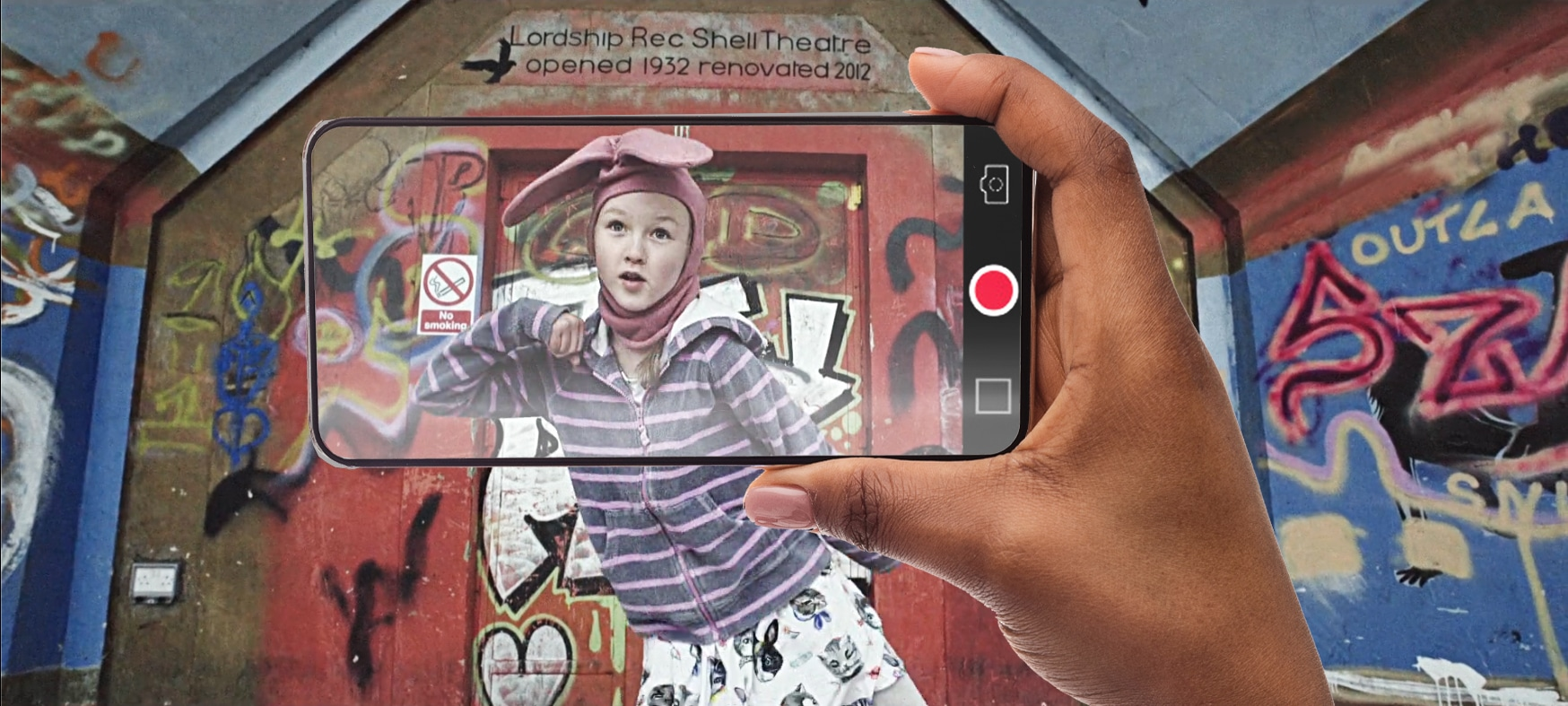 An image of a young girl dancing whilst wearing bunny ears. A mobile phone is filming her.